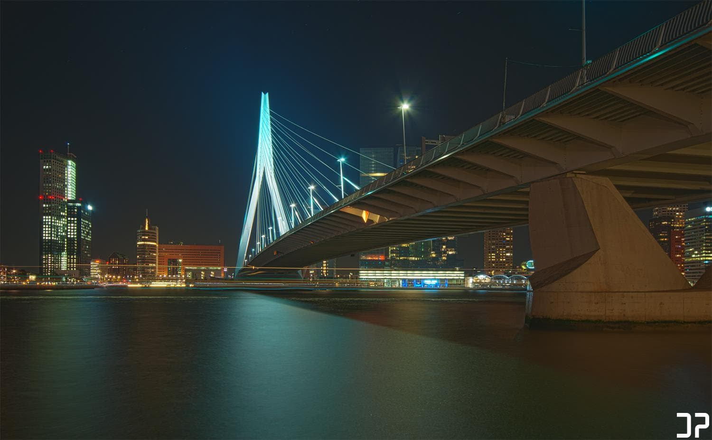 Avondfotografie van de Erasmusbrug in Rotterdam, en de skyline van de Wilhelminapier, vanaf de overzijde van de Nieuwe Maas.